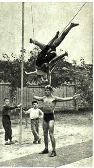 Это фото сделано во время репетиции силовых акробатов Е. Ржавинского, В. Стыкана и В. Ефремовой. Они исполняют трудный, пока никем не повторимый трюк. Стыкан (верхний) делает стойку на одной руке на голове Е. Ржавинского (нижний). При этом у него в «обмотке» находится  партнерша.