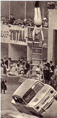 Акробат Сонни исполняет стойку на лестнице, установленной на едущей на двух колесах автомашине.