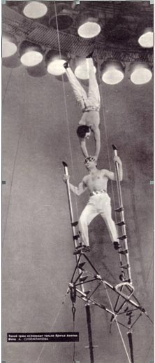 Братья Акопян.  Акробат, опираясь попеременно на лестницы, поднимается вверх. На его голове, в момент подъема, партнер делает на руках стойк