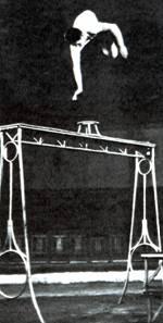 Эквилибрист В. Головин, выступая на высоком пьедестале, исполняет сложные трюки.