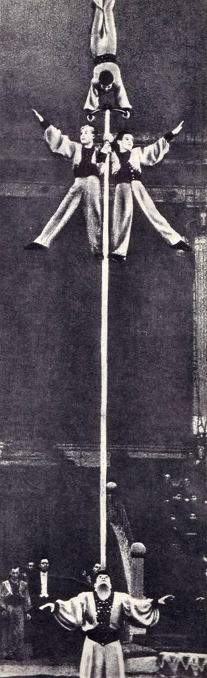 Милаев, держа на лбу шест со стоящим на нем партнером, пробегает через весь манеж и останавливается у самого барьера